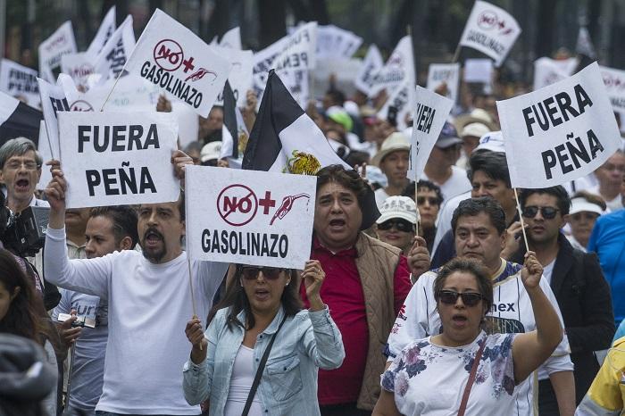 """CIUDAD DE MÉXICO, 01ENERO2017.- Decenas de ciudadanos, que se dijeron apartidistas, marcharon sobre Paseo de la Reforma en rechazo al aumento que sufrió la gasolina a partir de el primer minuto de este año. Con el """"gasolinazo"""", el combustible tipo Magna subirá 14 por ciento para costar 15.99 pesos por litro. La Premium aumentará 20 por ciento para cotizarse en 17.79 por litro. Y el diésel incrementará 16.5 por ciento para llegar a los 17.05 pesos. FOTO: ISAAC ESQUIVEL /CUARTOSCURO.COM"""