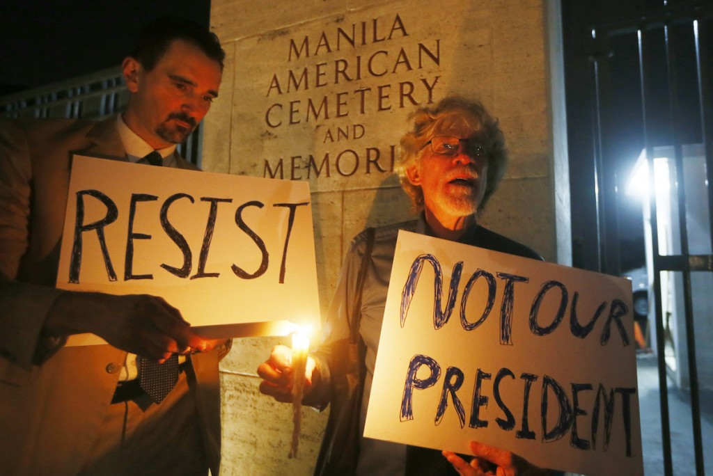 American residents in the Philippines Gabriel Ortiz, left, and Donald Goertzen display placards during a candlelight vigil at the American Cemetery to protest the inauguration of President-elect Donald Trump as the 45th President of the United States Friday, Jan. 20, 2017 in suburban Taguig city east of Manila, Philippines.(AP Photo/Bullit Marquez)