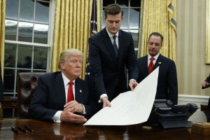 White House Chief of Staff Reince Priebus, right, watches as White House Staff Secretary Rob Porter, center, hands President Donald Trump a confirmation order for James Mattis as defense secretary, Friday, Jan. 20, 2017, in the Oval Office of the White House in Washington. (AP Photo/Evan Vucci)